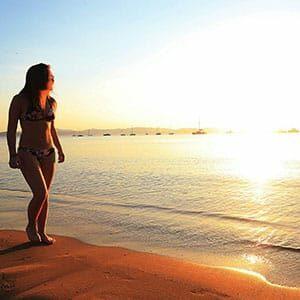 Image d'une Femme marchant sur la plage au soleil couchant