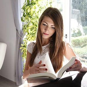 Photo d'une femme qui lit un livre avec le soleil derrière