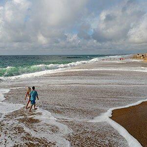 Photo avec drone d'un couple marchant dans l'eau à Biscarosse