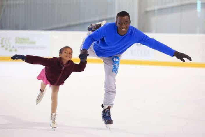 Photo d'un père et sa fille faisant du patin