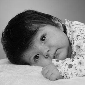 Photo d'un nouveau né en noir et blanc allongé