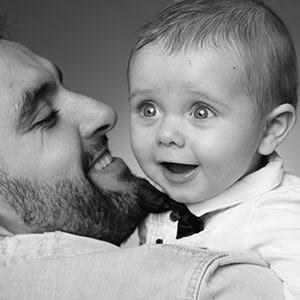 Image d'un bébé étonné en noir et blanc sur l'épaule de son papa