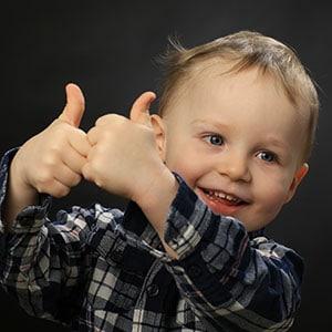 Photo d'un enfant montrant ses pouces en studio à Grenoble