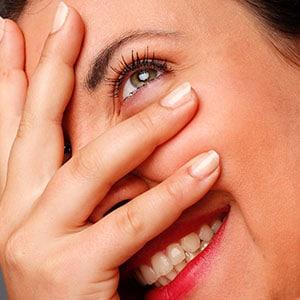 Photo d'une femme qui sourit et met la main devant son visage